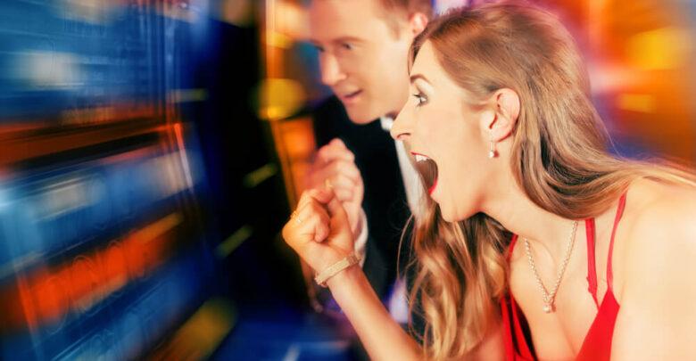 Gambling couple in Casino or amusement arcade on slot machine winning