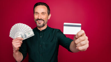 Close-up portrait of his he nice cheery bearded man holding in hand giving you freelance plastic card withdrawal isolated on bright vivid shine vibrant maroon burgundy marsala red color background