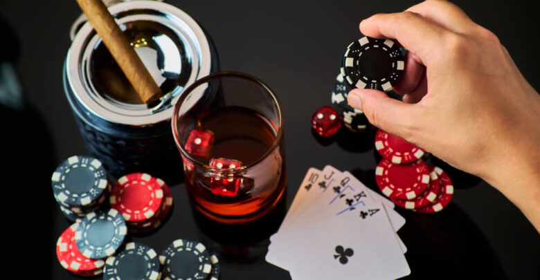 Casino chips, playing cards, glass of whiskey and dices on dark reflective background