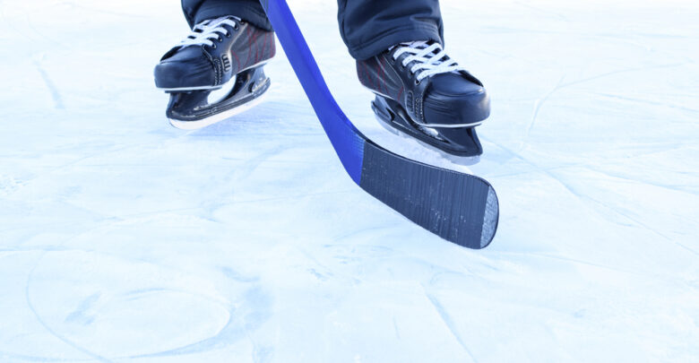 A man in skates on ice with a hockey stick. View only feet.