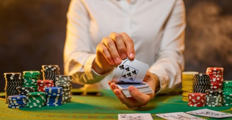 The girl of the croupier lays out the cards on the green cloth of the poker table. Stacks of chips. Casino, gambling, poker, gambling business, leisure, nightclub, hobby.